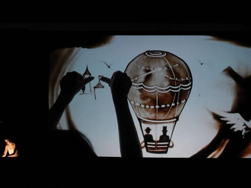 Eine beleuchtete Glasplatte, darauf ein Heißluftballon aus Sand