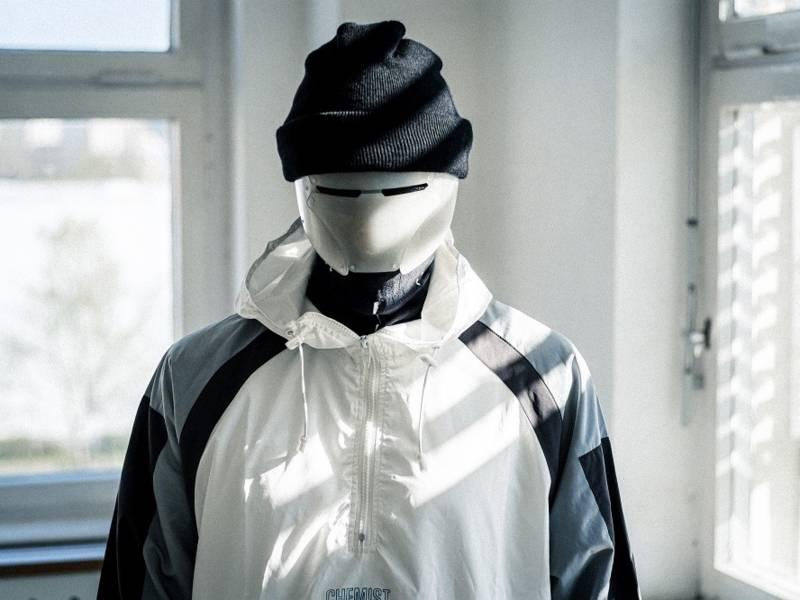 Eine Person mit schwarzer Mütze und einer weißen Maske auf, steht in einem Raum mit einer sportlichen Jacke an.