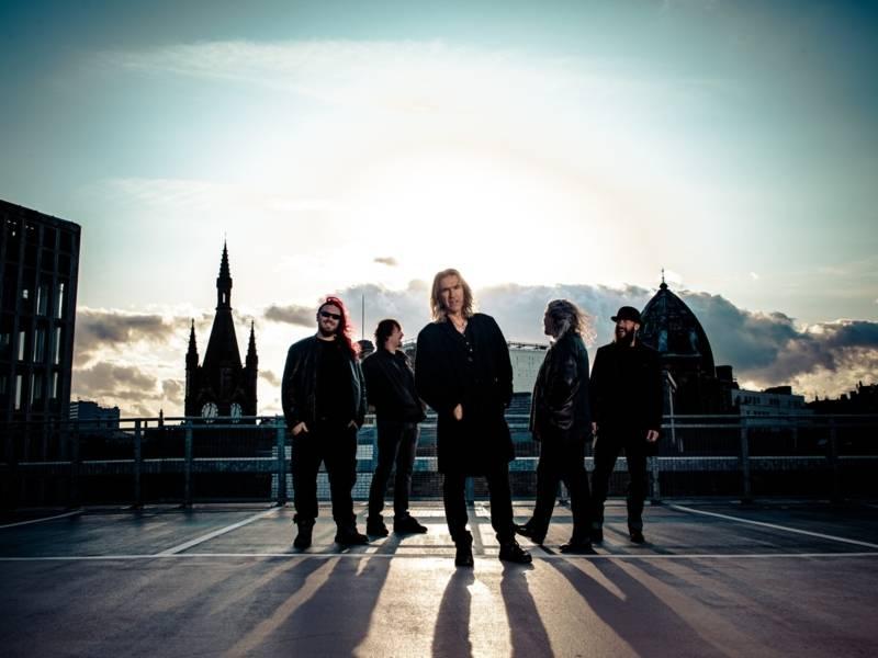 Fünf Männer in schwarzer Kleidung stehen auf einem Parkplatz. Die Sonne ist hinter ihnen und wirft Schatten nach vorne.