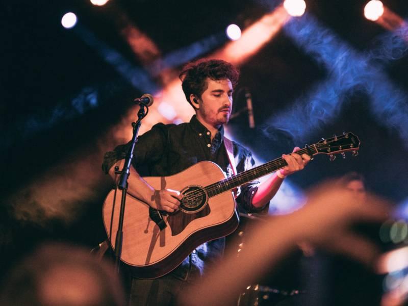 Ein Musiker steht mit der Gitarre auf einer Bühne. Das Foto wurde von unten aufgenommen und alles um den Musiker herum ist verschwommen.