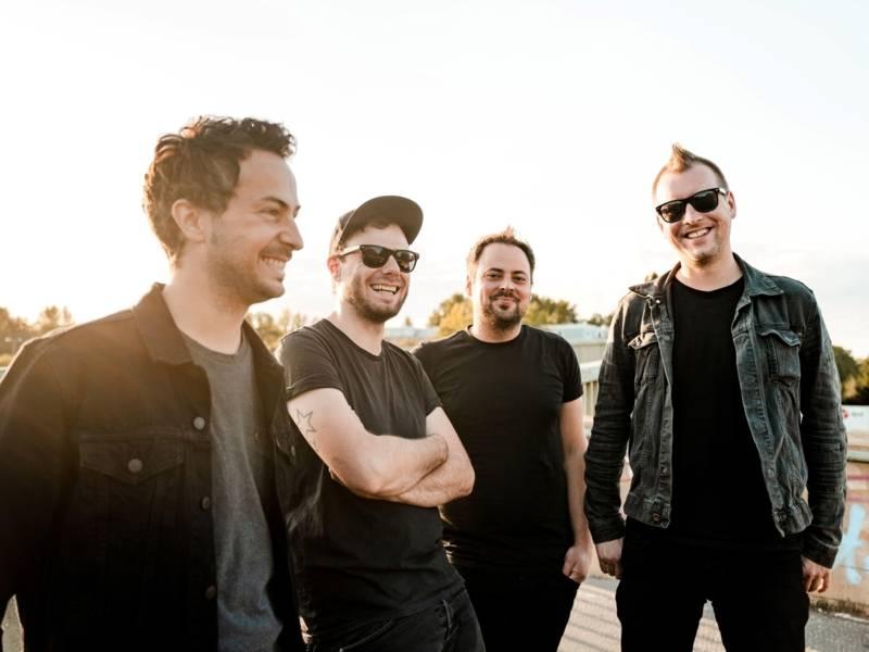 Vier Männer in schwarzer Kleidung stehen draussen im Sonnenlicht. Sie lachen sich gegenseitig an.