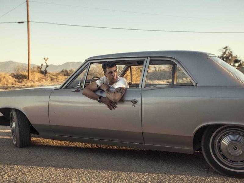 Ein Mann in einem weißen T-Shirt und Arm Tattoos sitzt in einem grauen Auto. Er ist aus dem Fenster gelehnt und schaut nach hinten.
