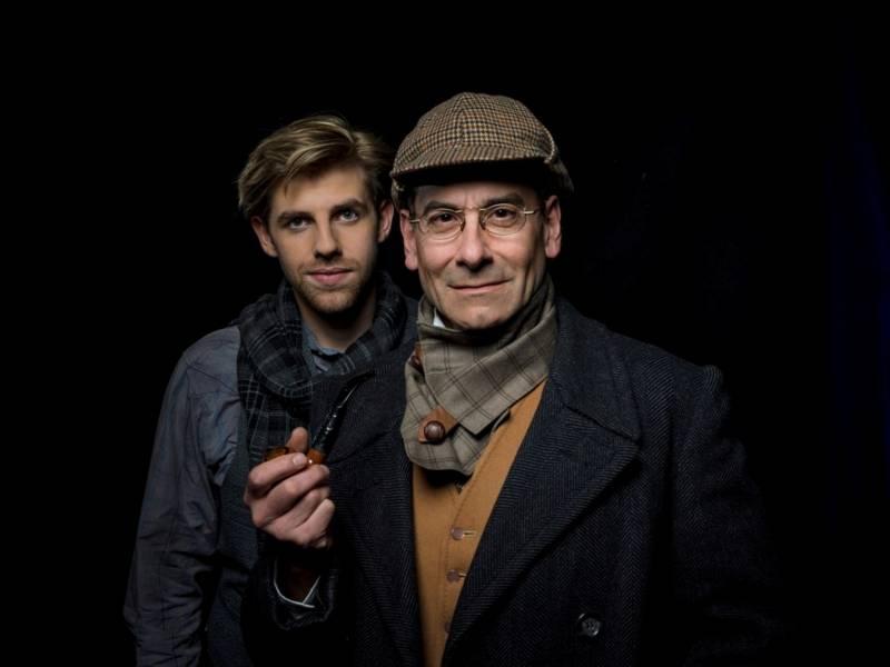 Ein Mann mit einer braunen Mütze und Brille hält eine Pfeife in der rechten Hand. Hinter ihm steht ein jüngerer Mann in blauem Jeanshemd und Schal.