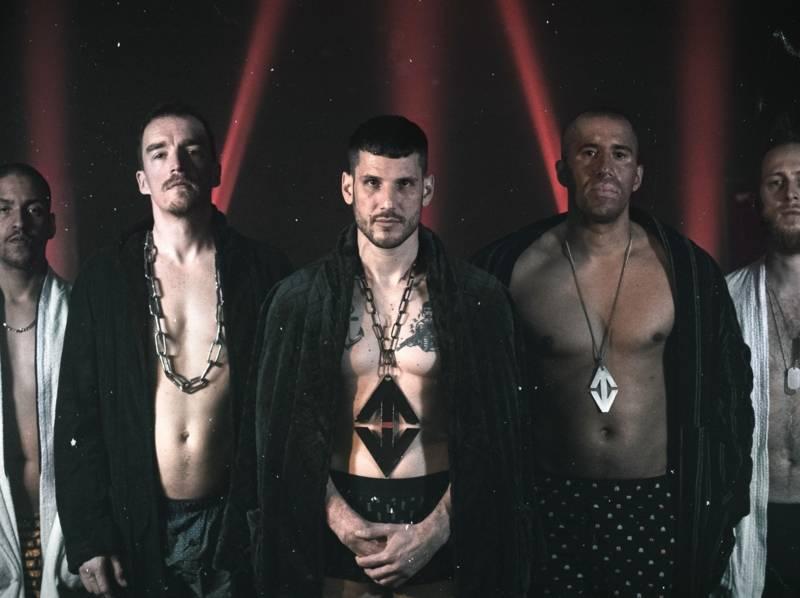 Fünf Männer stehen versetzt nebeneinander und schauen ernst. Sie sind Oberkörperfrei und tragen nur einen offenen Bademantel und Boxershorts und dazu eine große Kette.