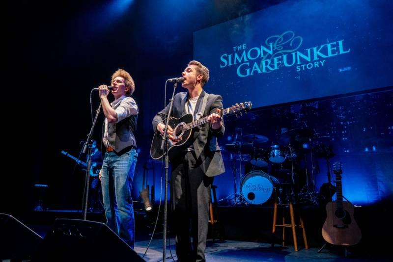 Zwei Männer stehen mit Mikrofonen auf der Bühne, im Hintergund der Name ihrer Show auf einer großen Leinwand. Der eine Mann spielt Gitarre.