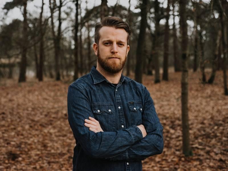 Ein Mann mit Vollbart und Jeanshemd steht im Wald und hält seine Arme verschränkt.