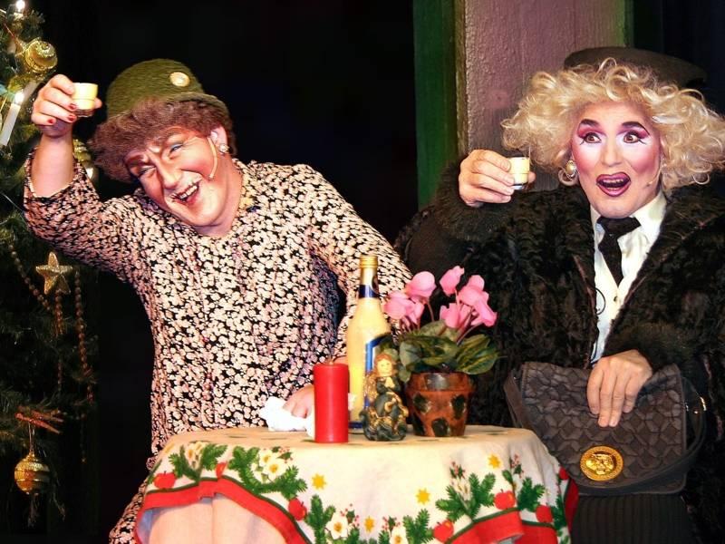 Zwei Männer als Seniorinnen verkleidet sitzen an einem Tisch.