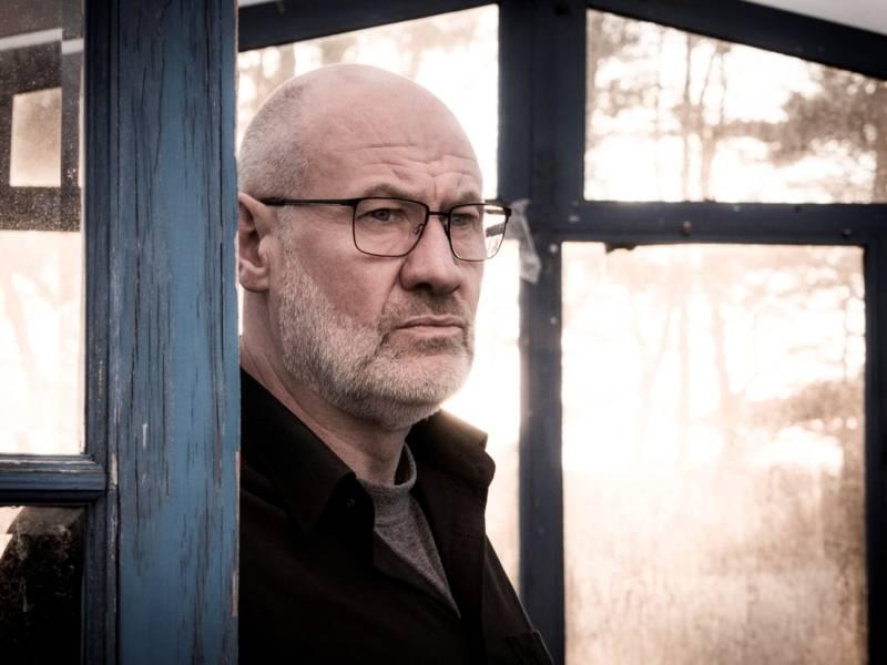 Ein Mann mit Brille und schwarzem Hemd blickt nach rechts