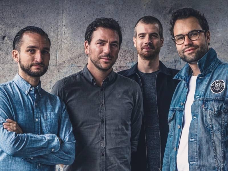 Vier Männer, drei davon in Jeanshemden schauen in die Kamera.
