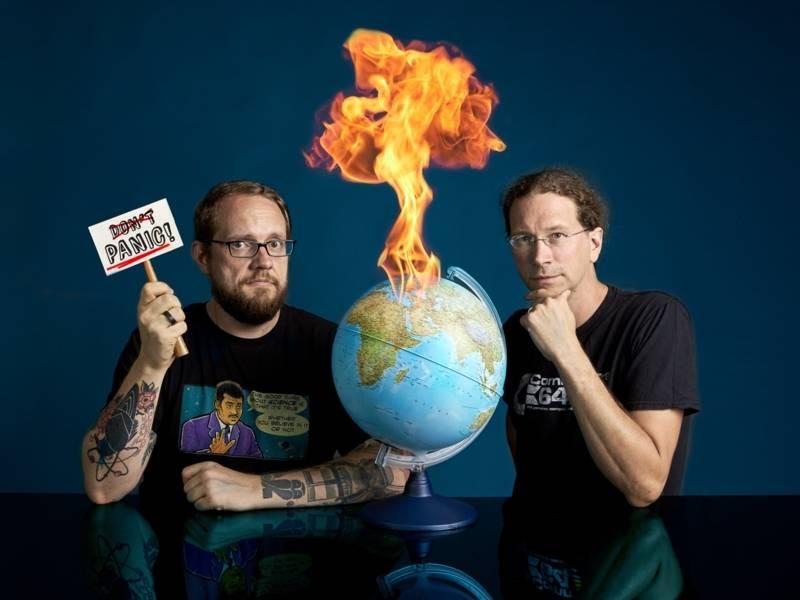 """zwei Männer mit schwarzen T-Shirts. Zwischen ihnen steht ein Globus, der in Falmmen steht. Auf einem Schild steht """"panic""""."""