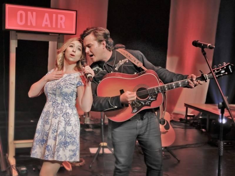 Eine Frau und ein Mann in Cowboy Klamotten singen auf einer Bühne.