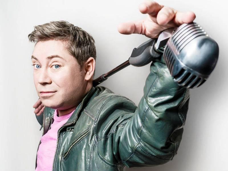 Mann mit einem quer in den Nacken gelegten Mikrofonständer