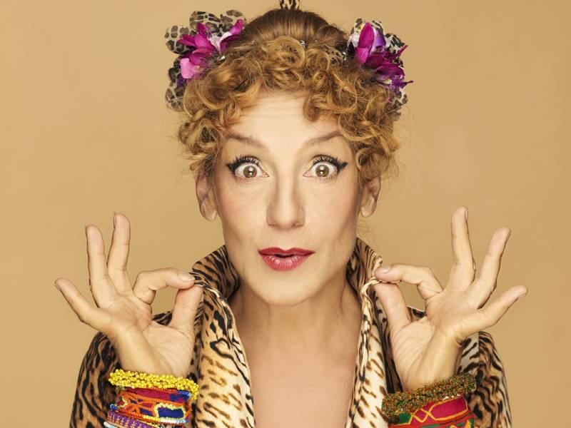 Eine Frau mit bunten Armbändern und Blumen in den Haaren