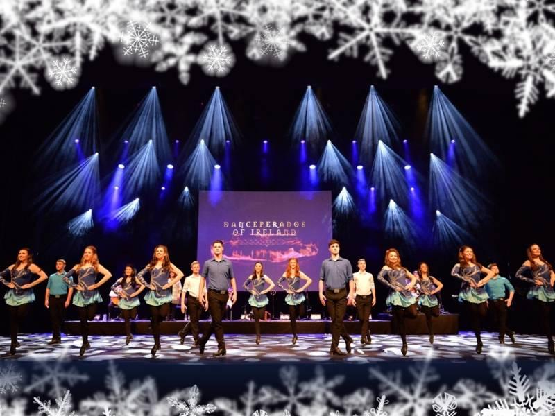Tänzer und Tänzerinnen stehen auf einer Bühne. Sie tragen blaue Kostüme.