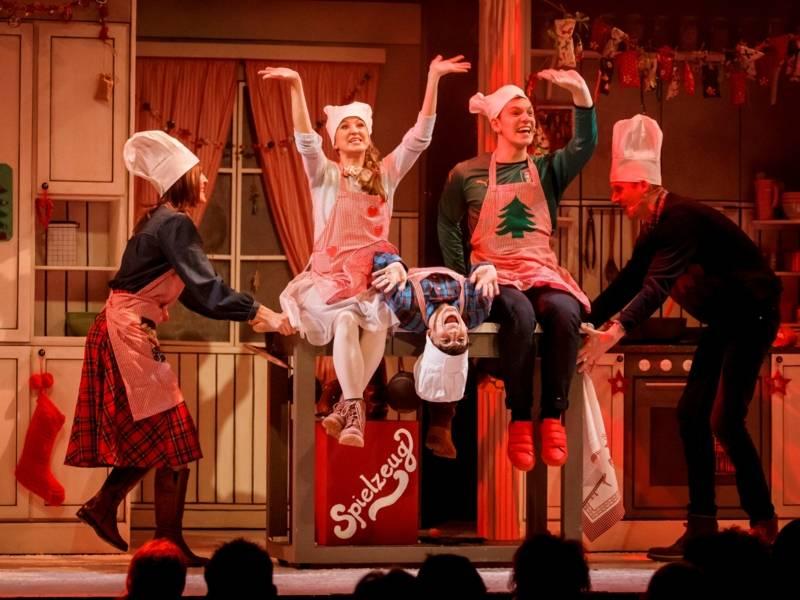 Vier Musicaldarstellende stehen auf der Bühne.  Alle tragen Weihnachtsschürzen und Kochmützen.