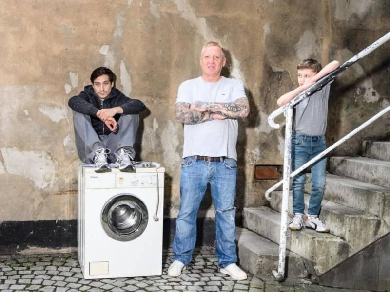 Ein Mann sitzt auf einer Waschmaschine. Daneben steht ein weiterer Mann und ein Junge auf einer Treppe.