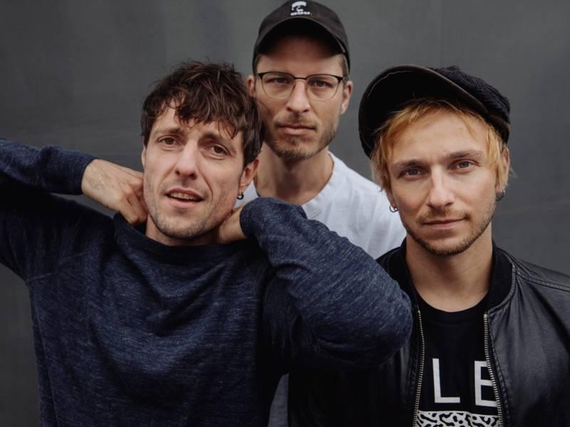 Drei junge Männer schauen in die Kamera, einer trägt eine Brille und zwei eine Mütze.