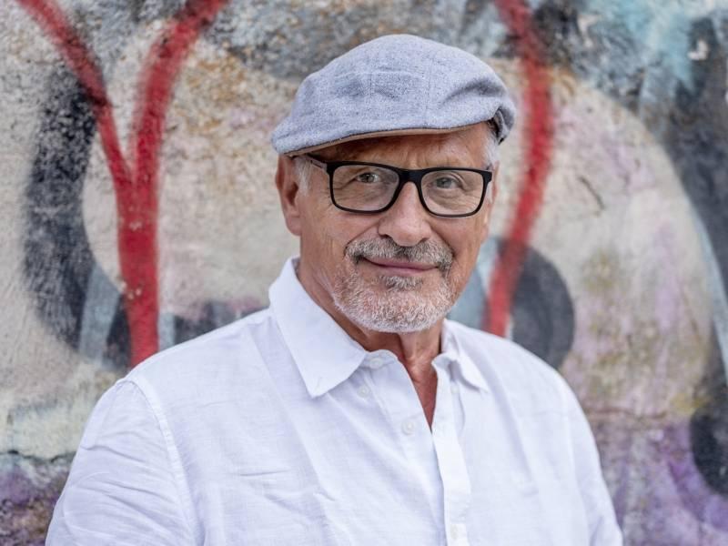 Ein Mann mit Brille und weißen Haaren, mit einem chlichten hemd steht vor einer Graffiti Wand.