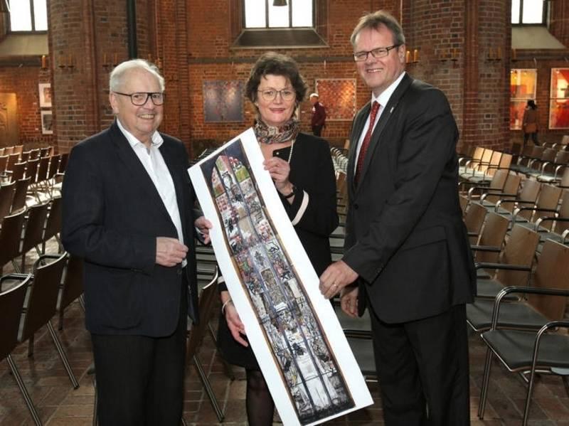 Zwei Männer und eine Frau halten eine Grafik, die ein Kirchenfenster zeigt.