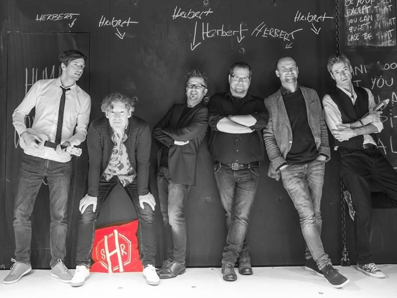 """Sechs Männer stehen an einer Wand. Auf alle zeigt jeweils ein Pfeil mit der Beschriftung """" Herbert""""."""
