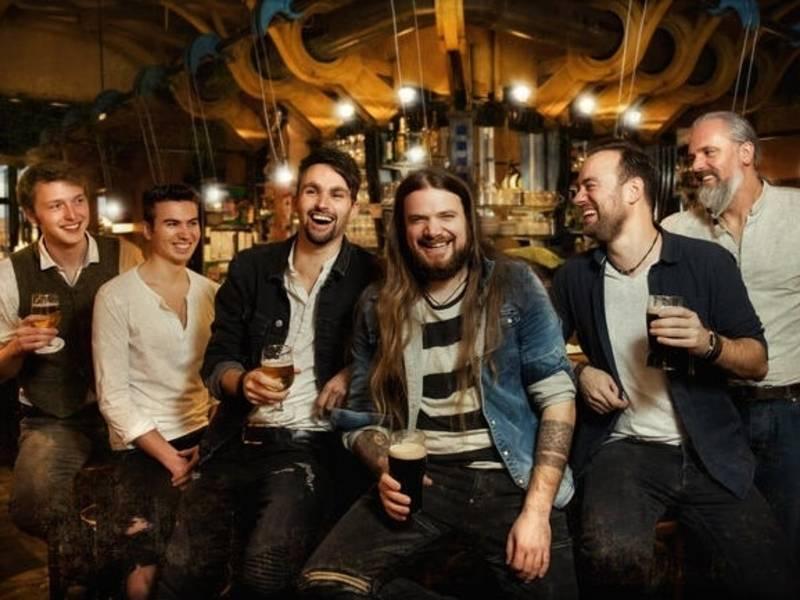 Sechs Männer von alt bis jung sitzen in einer Bar, die Holzelemente hat und trinken Bier. Sie lachen sich gegenseitig an und einige in die Kamera.