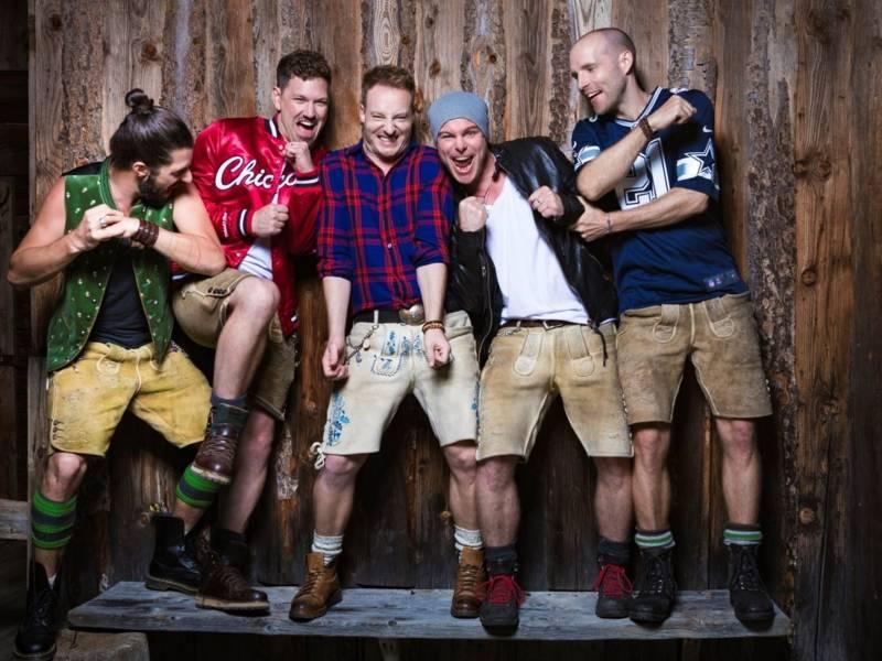 Fünf junge Männer in bunter Kleidung stehen auf einer Holzbank und versuchen sich gegenseitig ruunterzuwerfen.