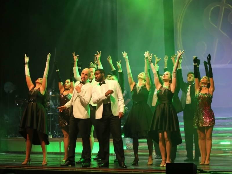 viele Tänzer und Tänzerinnen auf einer Bühne. Sie halten die Hände in die Luft.