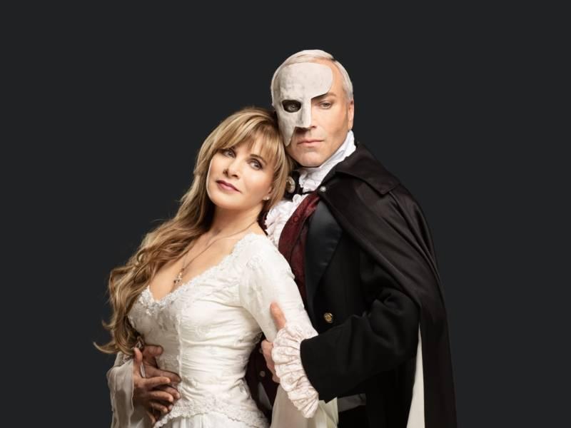 Frau mit blonden Harren und einem Kleid, wird von einem Mann mit Maske gehalten.