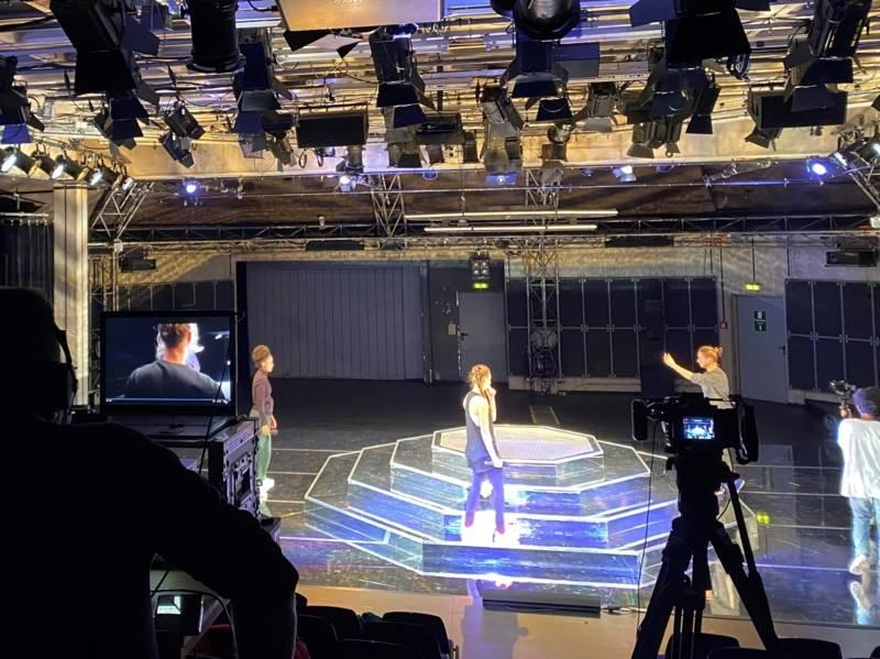 Drei Personen auf einer Bühne, zwei Personen mit Kameras filmen diese