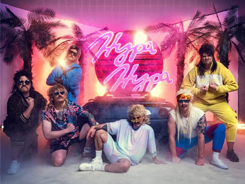Mit Sand auf dem Boden und Palmen im Hintergrund sowie einem Hypa Hypa Neonzeichen sin die sechs Jungs auf dem Bild zu sehen. Sie tragen alle bunte Kleidung mit Perrücken und großen Sonnenbrillen.