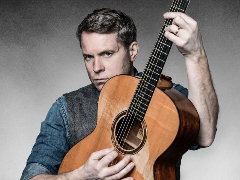 Mann, der eine Gitarre hält und ernst guckt.