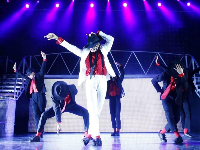 Männer in Schwarz-roten Anzügen auf der Bühne, Ein Michael Jackson-Immitator steht in der Mitte.