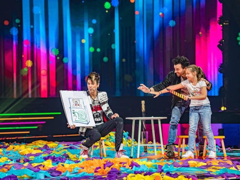 bunte Bühne. Ein Mann hält ein Bild in der Hand. Ein anderer Mann redet mit einem Kind, welches auf das Bild zeigt.
