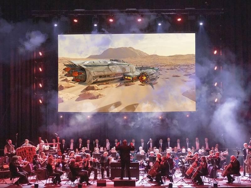 Großes Orchester auf einer Bühne, im Hintergrund Bild einer Wüstenlandschaft mit einem Raumschiff