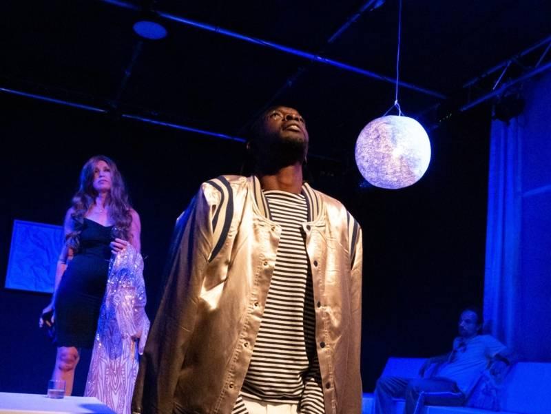 Ein Mann steht auf einer Bühne und blickt nach oben.