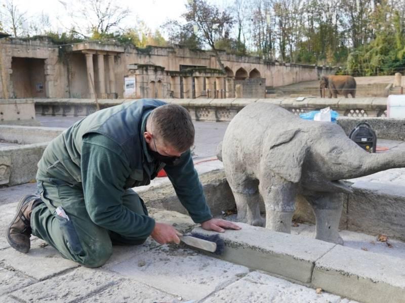 Ein Mann spachtelt am Elefantenbrunnen.