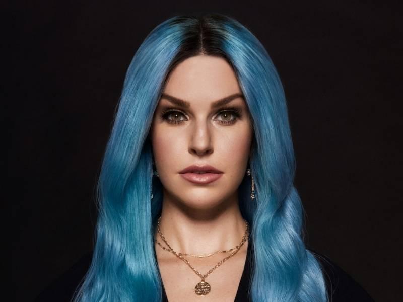 Eine Frau mit blauen Haaren vor einem schwarzen Hintergrund.