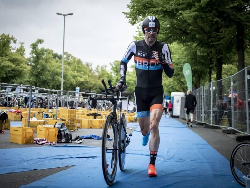 Mann im Sportdress läuft und schiebt dabei ein Rennfahrrad