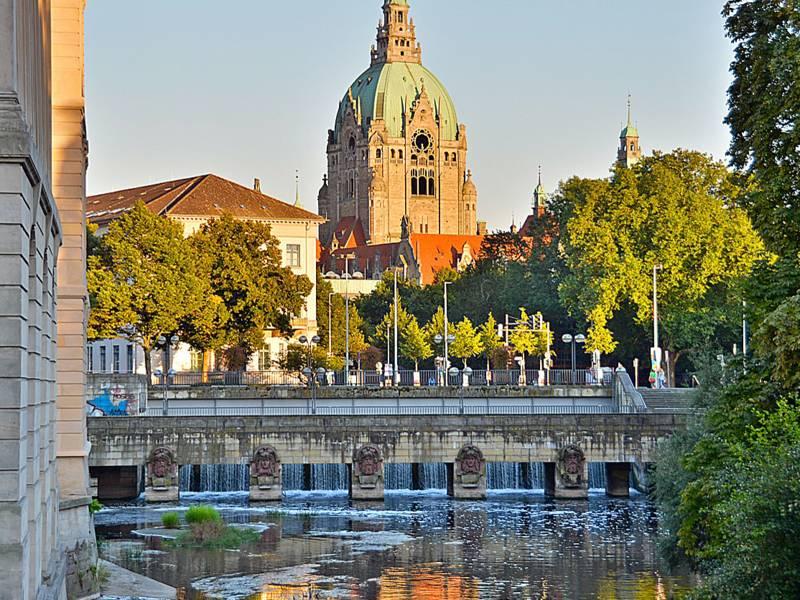 Autobrücke über Gewässer mit historischem Gebäude mit Kuppeldach im Hintergrund.