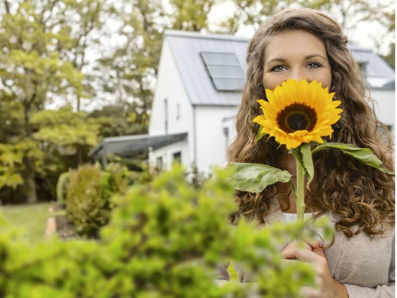 Frau Hält eine Sonnenblume vor ihr Gesicht