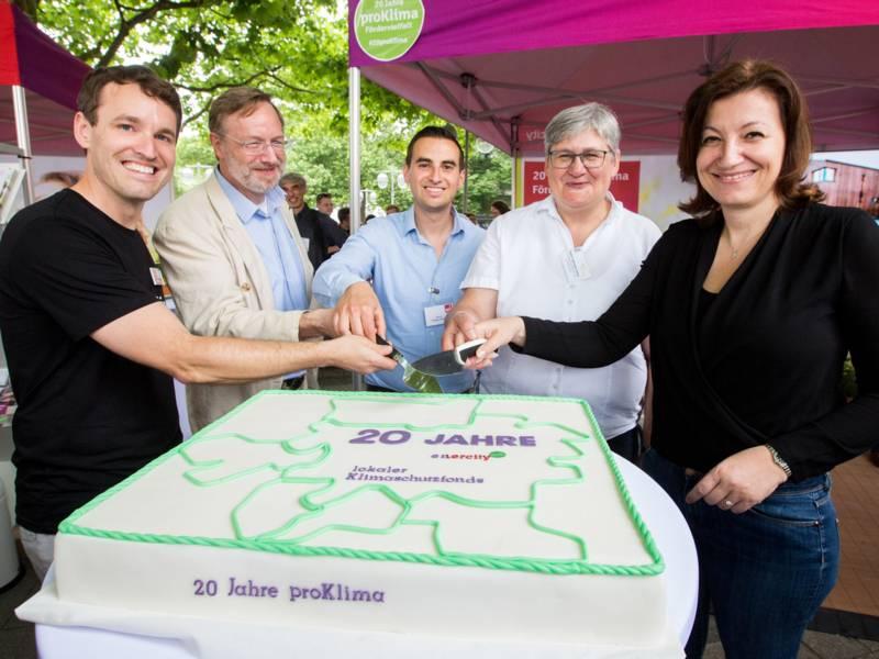 """Zwei Frauen und drei Männer schneiden symbolisch eine Torte mit der Aufschrift """"20 Jahre proklima"""" an."""