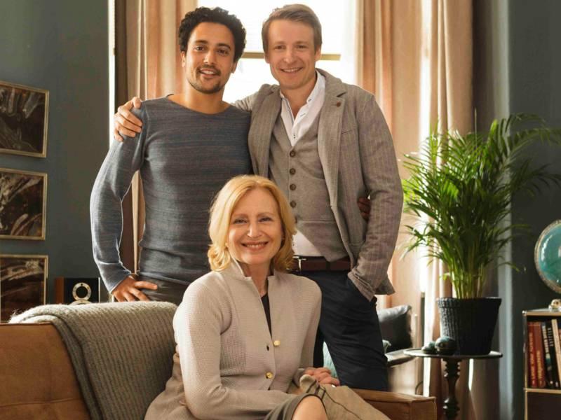 Zwei Männer stehen in einem Wohnzimmer hinter einer älteren Frau, die auf einem Sofa sitzt.
