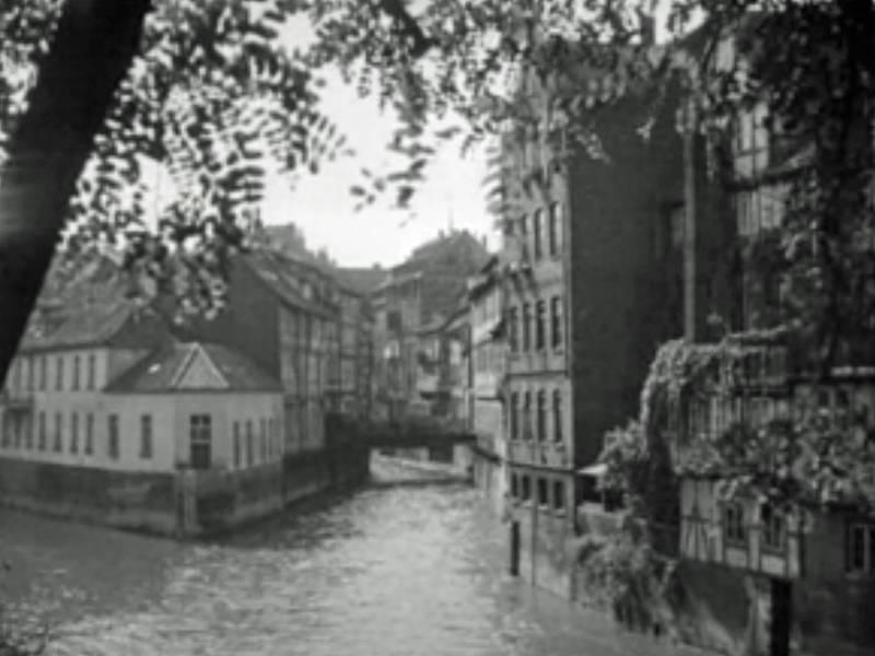 Historisches Foto: Mehrgeschossige Wohnhäuser auf einer Flußinsel und an den Ufern.
