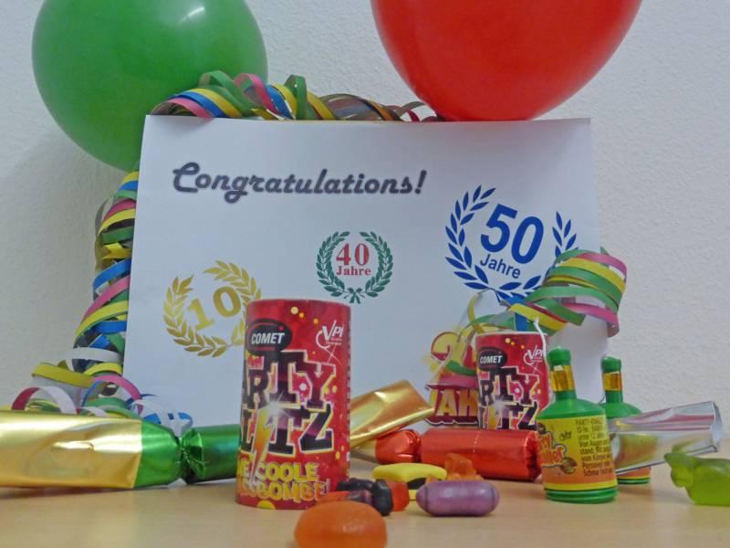Tischfeuerwerk, Luftschlangen und Luftballons um ein Schild mit Jubiläumszahlen