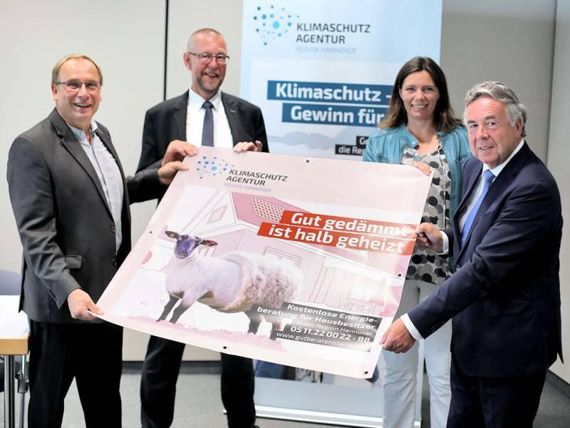 Eine Frau und drei Männer halten ein Plakat.