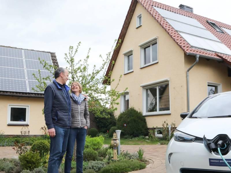 Frau und Mann stehen Arm in Arm vor einem Haus, im Vordergrund wird ein Elektroauto geladen.