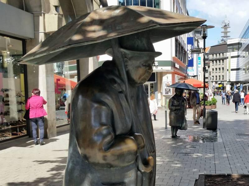 Plastiken einer Frau und eines Mannes mit Regenschirmen in einer Fußgängerzone.