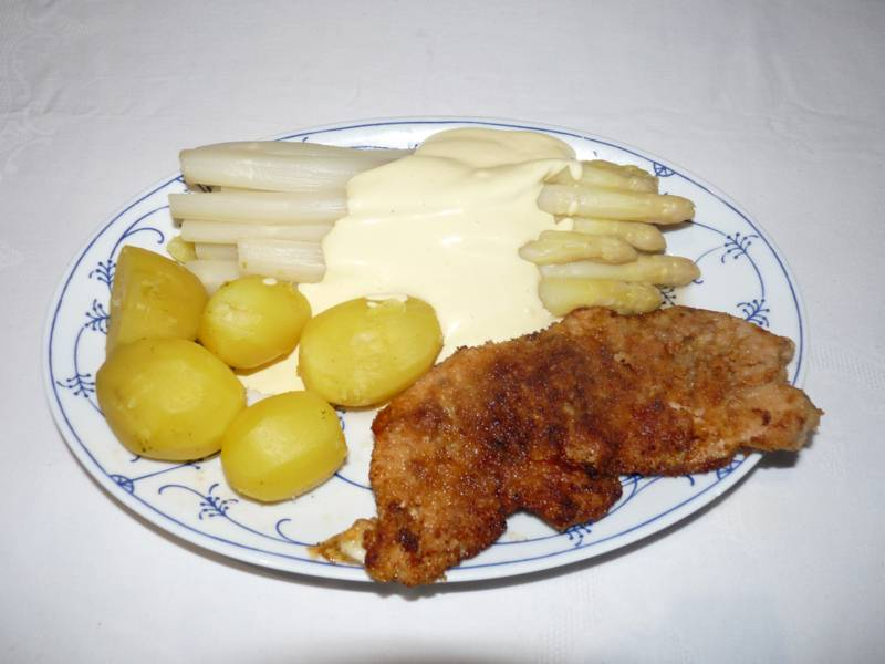 Teller mit Kartoffeln, Spargel mit Soße und Schnitzel