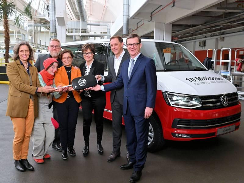 Menschengruppe einen übergroßen Autoschlüssel haltend vor einem rot-weißen VW Bulli.