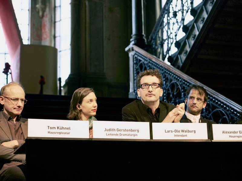 Vier Personen bei einer Pressekonferenz.